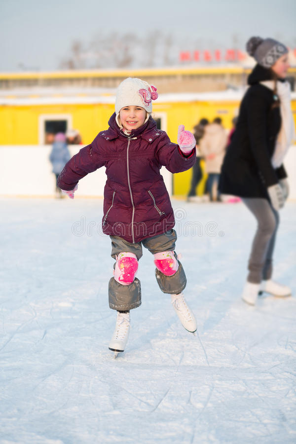 Uśmiechnięta mała dziewczynka jeździć na łyżwach przy lodowiskiem w kolanowych ochraniaczach obraz stock