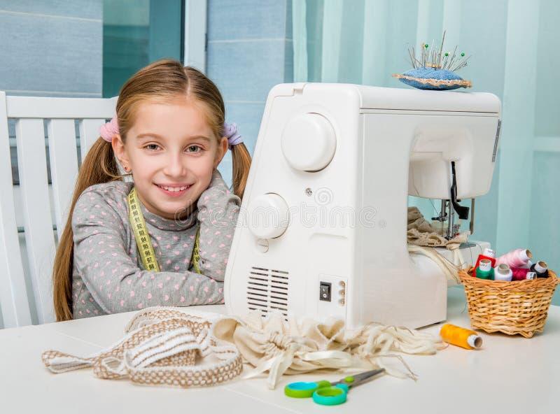 Uśmiechnięta mała dziewczynka przy stołem z szyć obraz stock