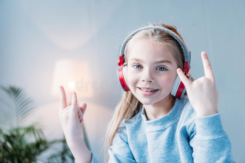 Uśmiechnięta mała dziewczynka w hełmofonach pokazuje skała znaki obraz stock