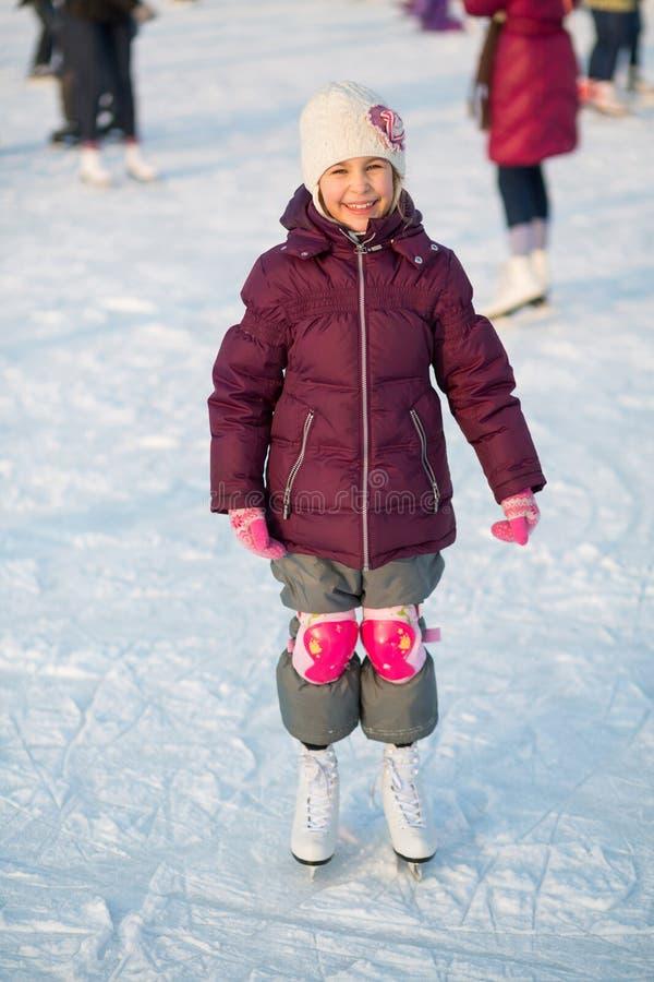Uśmiechnięta mała dziewczynka w kolanowych ochraniaczów jeździć na łyżwach zdjęcie royalty free
