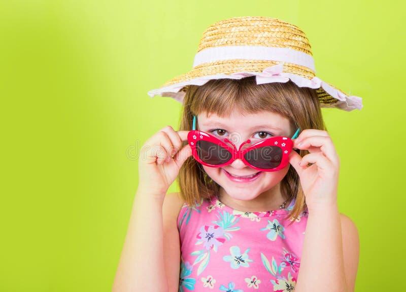Uśmiechnięta mała dziewczynka w słomianym kapeluszu i okularach przeciwsłonecznych obraz royalty free