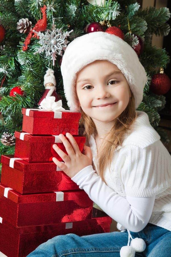 Uśmiechnięta mała dziewczynka w Santa kapeluszu z prezentami obraz stock