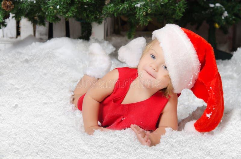 Uśmiechnięta mała dziewczynka w Santa kostiumu na śniegu zdjęcie royalty free