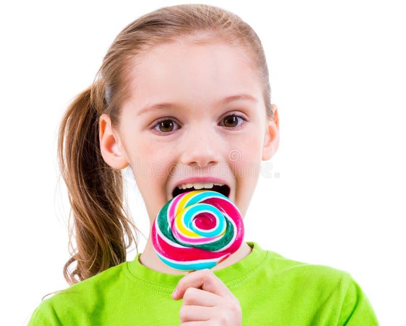 Uśmiechnięta mała dziewczynka w zielonym koszulki łasowaniu barwił cukierek obraz stock