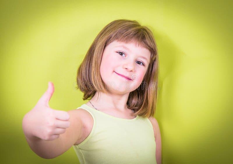 Uśmiechnięta mała dziewczynka z aprobatami obrazy stock