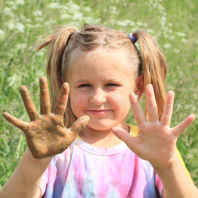 Uśmiechnięta mała dziewczynka z błotnistą ręką obrazy royalty free