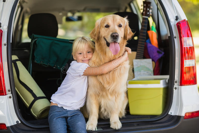 Uśmiechnięta mała dziewczynka z jej psem w samochodowym bagażniku zdjęcie royalty free
