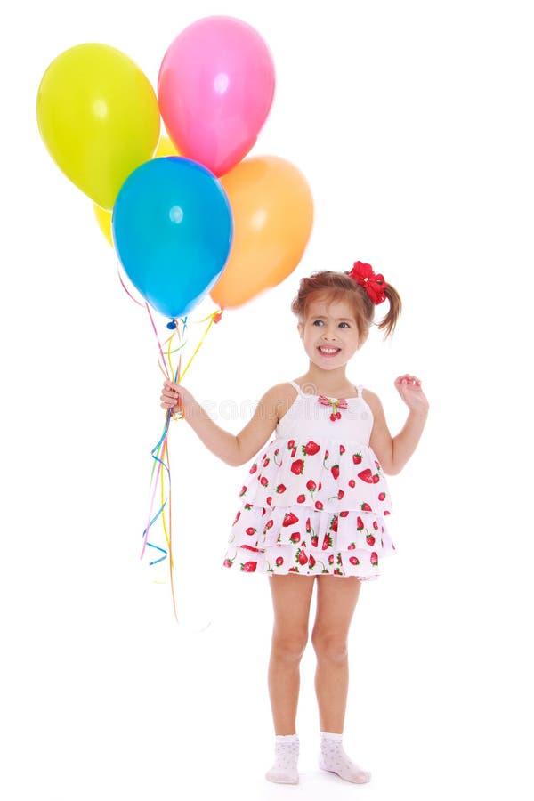 Uśmiechnięta mała dziewczynka z koralikami w ich rękach fotografia royalty free