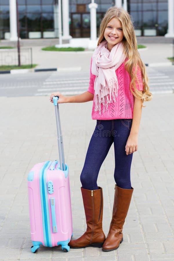 Uśmiechnięta mała dziewczynka z menchii podróży walizką obrazy stock