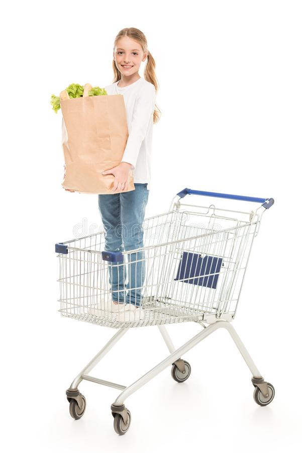 uśmiechnięta mała dziewczynka z papierowej torby pozycją w wózek na zakupy obraz royalty free