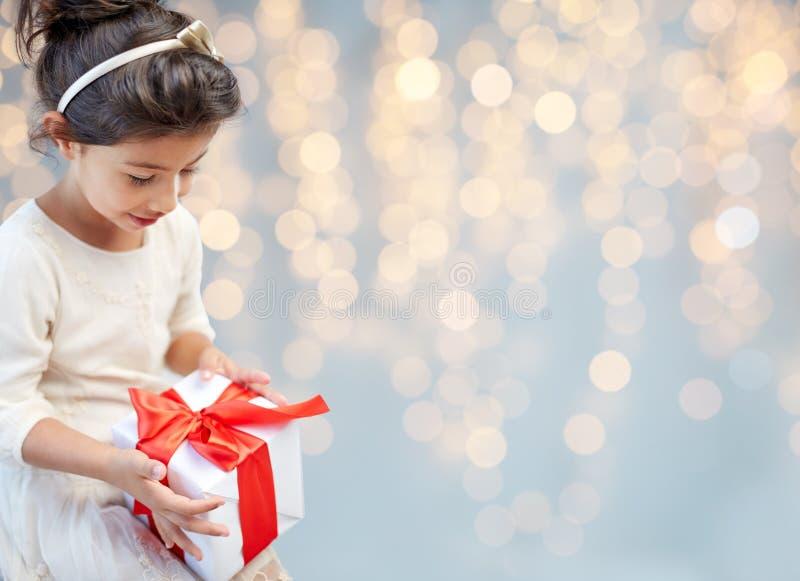 Uśmiechnięta mała dziewczynka z prezenta pudełkiem nad światłami fotografia royalty free