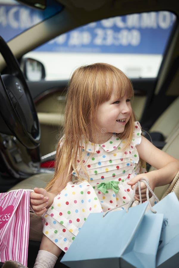 Uśmiechnięta mała dziewczynka z zakupy w samochodzie obrazy royalty free