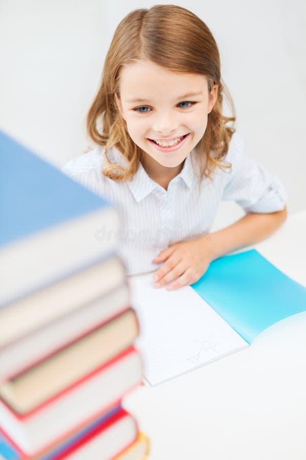 Uśmiechnięta mała studencka dziewczyna z dużo rezerwuje obrazy royalty free