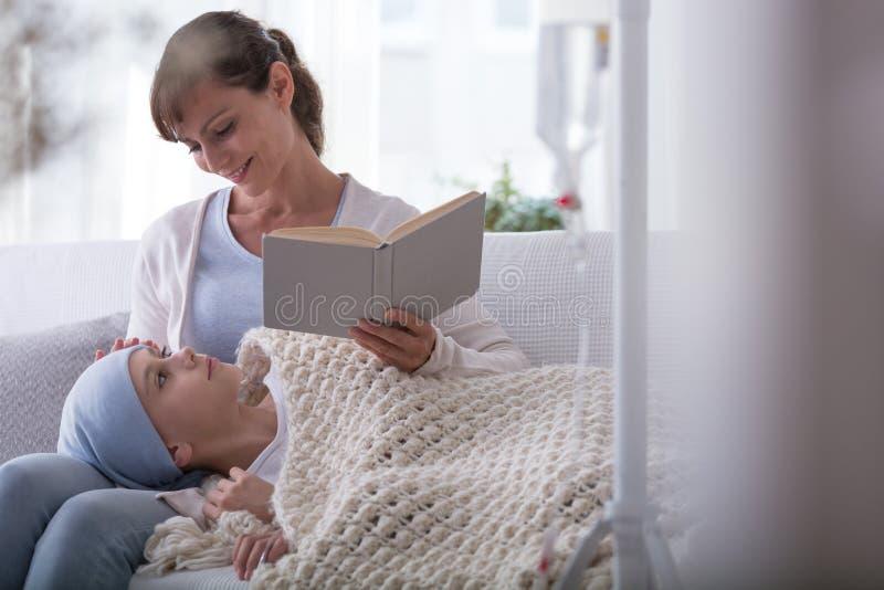 Uśmiechnięta macierzysta czytelnicza książka dziecko z nowotworem jest ubranym chustkę na głowę zdjęcia stock