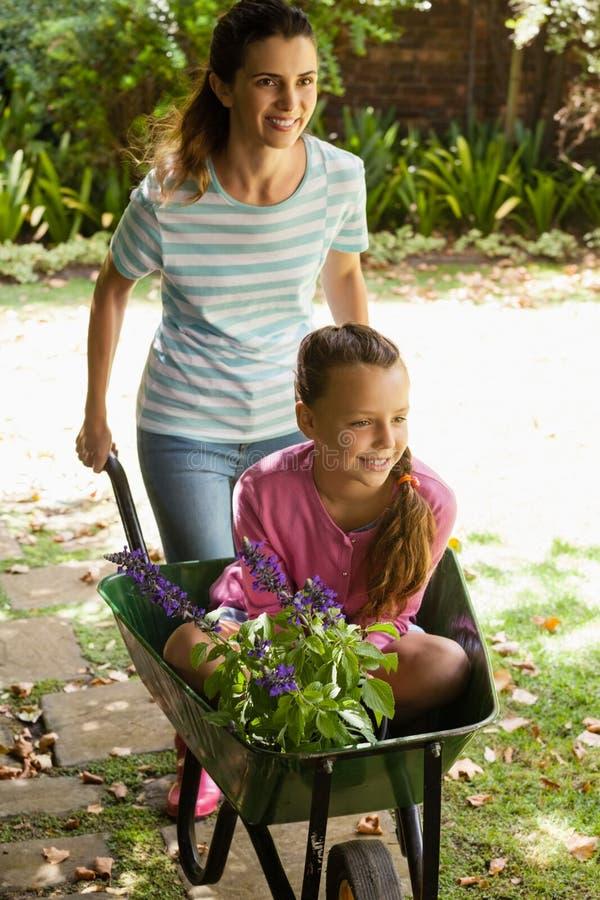Uśmiechnięta macierzysta dosunięcie dziewczyna siedzi w wheelbarrow z kwiatami obraz stock