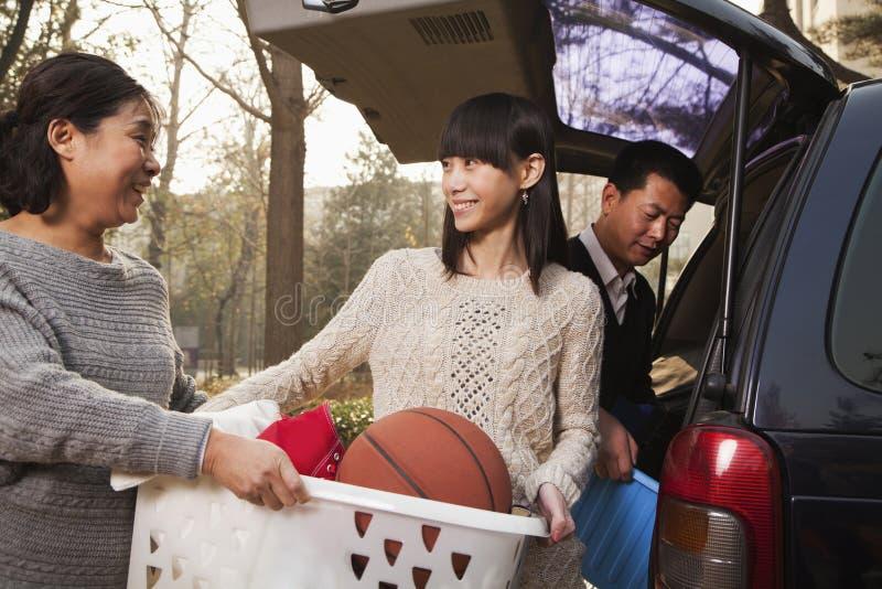 Uśmiechnięta macierzysta pomaga córka odpakowywa samochód dla szkoły wyższa, Pekin obraz royalty free