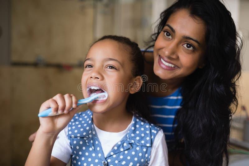 Uśmiechnięta macierzysta pozycja córką szczotkuje zęby w łazience zdjęcie royalty free