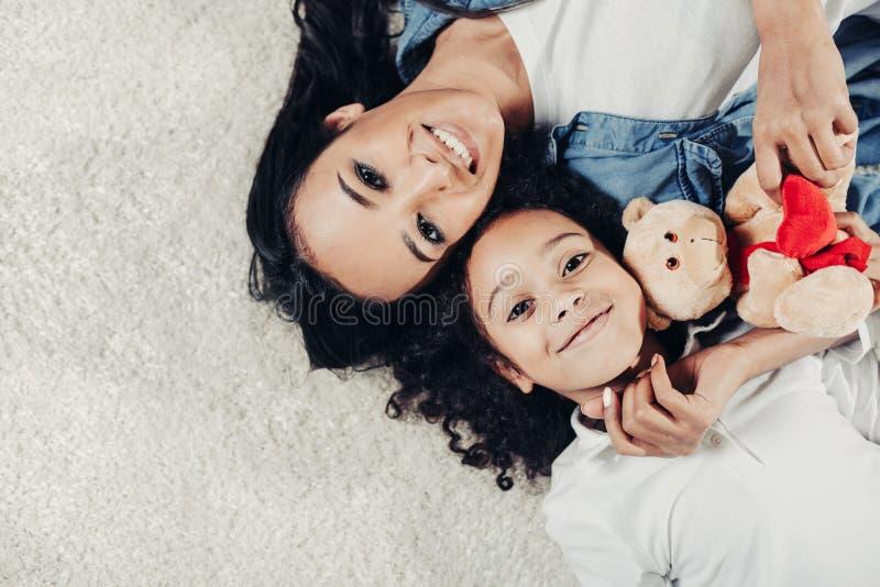 Uśmiechnięta mama i córka reposing na miękkim dywanie z zabawką fotografia royalty free