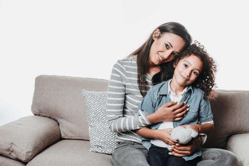 Uśmiechnięta mama i dziecko odpoczywa na kanapie i ściskać zdjęcie royalty free