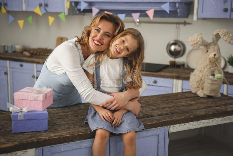 Uśmiechnięta matka i córka ściska indoors zdjęcia stock