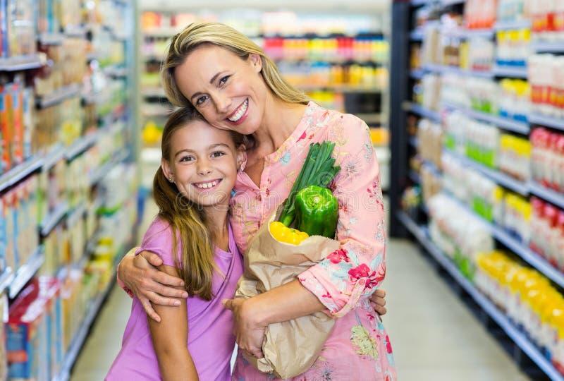 Uśmiechnięta matka i córka z sklep spożywczy torbą obrazy royalty free