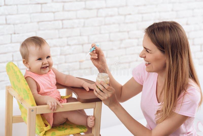 Uśmiechnięta matka karmi uśmiechniętego dziecka z puree obrazy stock