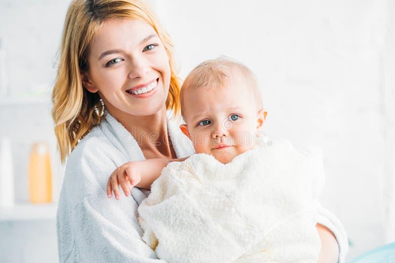 uśmiechnięta matka w bathrobe mienia małym dziecku zdjęcia stock
