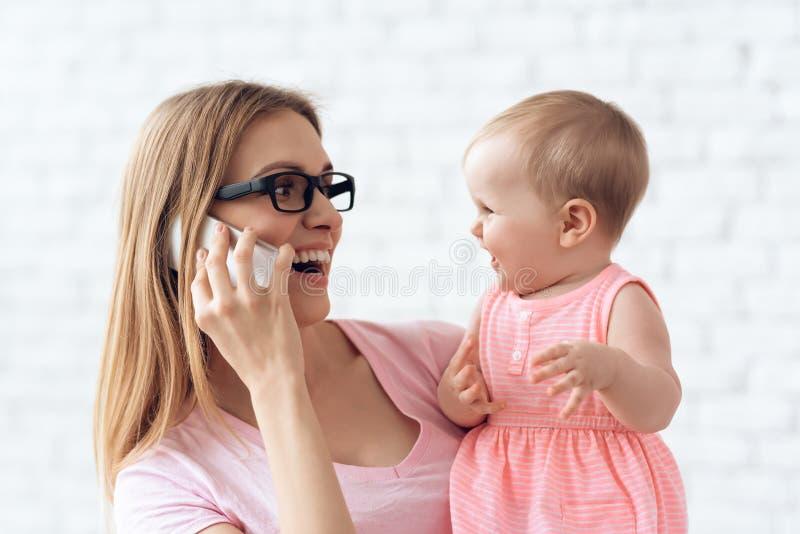Uśmiechnięta matka z małym dzieckiem używa smartphone zdjęcie royalty free