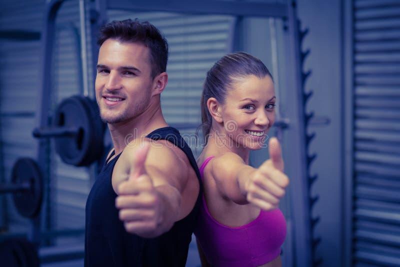 Uśmiechnięta mięśniowa para gestykuluje aprobaty fotografia stock