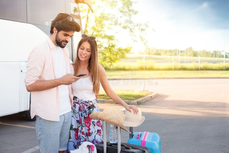 Uśmiechnięta miłości para z smartphone czekaniem zaczynać ich holi zdjęcie stock