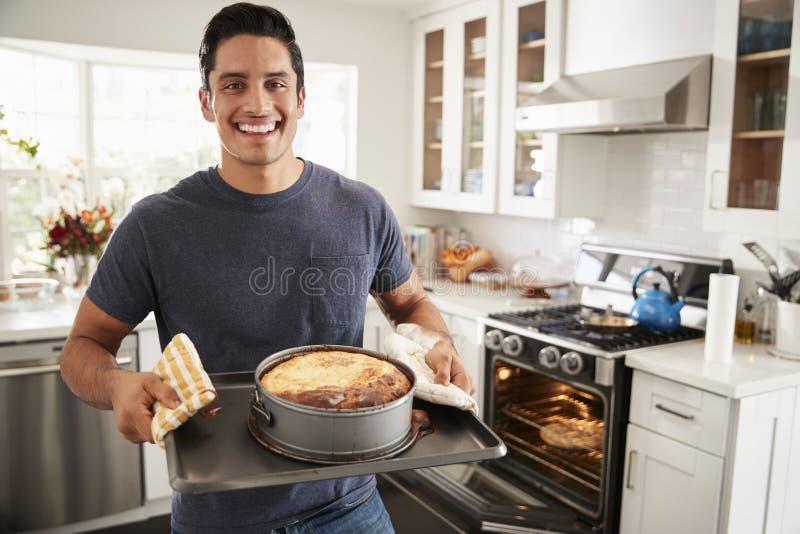 Uśmiechnięta millennial Latynoska mężczyzna pozycja w kuchni przedstawia tort piec kamera zdjęcie royalty free