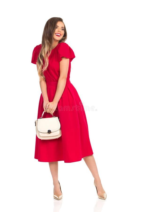 Uśmiechnięta Modna kobieta W rewolucjonistki sukni, Złocistych szpilkach I Beżowej kiesie, zdjęcia stock