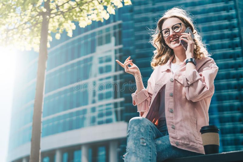 Uśmiechnięta modniś kobieta w szkłach siedzi outdoors i opowiadający na telefonie komórkowym Filiżanka kawy W tle jest drapacz ch obraz royalty free