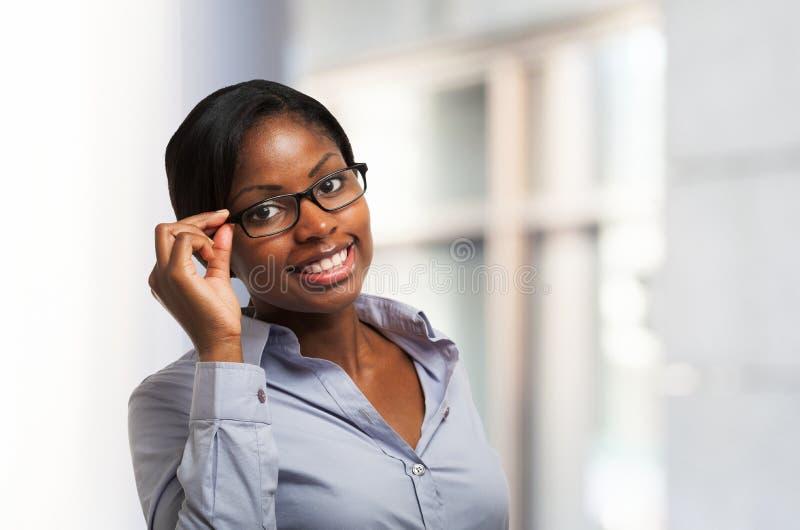 Uśmiechnięta murzynka trzyma jej eyeglasses zdjęcie stock