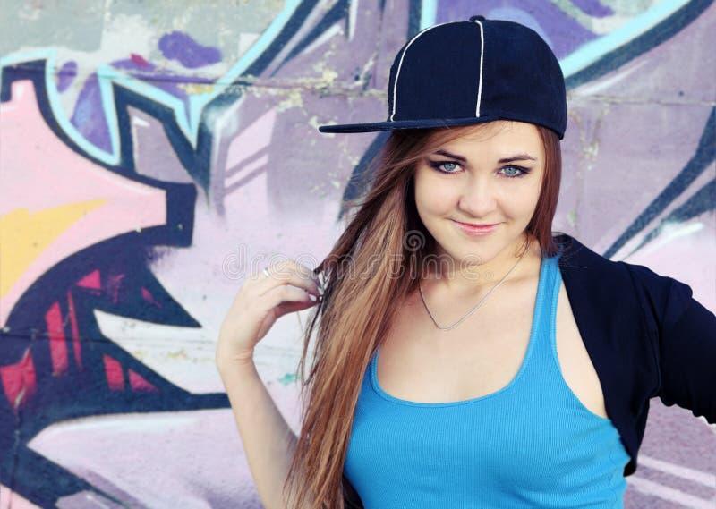 Uśmiechnięta nastolatek dziewczyna Pozuje blisko ściany obraz stock