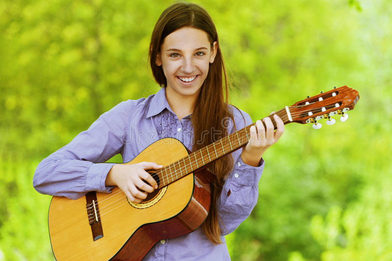 Uśmiechnięta nastoletnia dziewczyna bawić się gitarę obrazy stock
