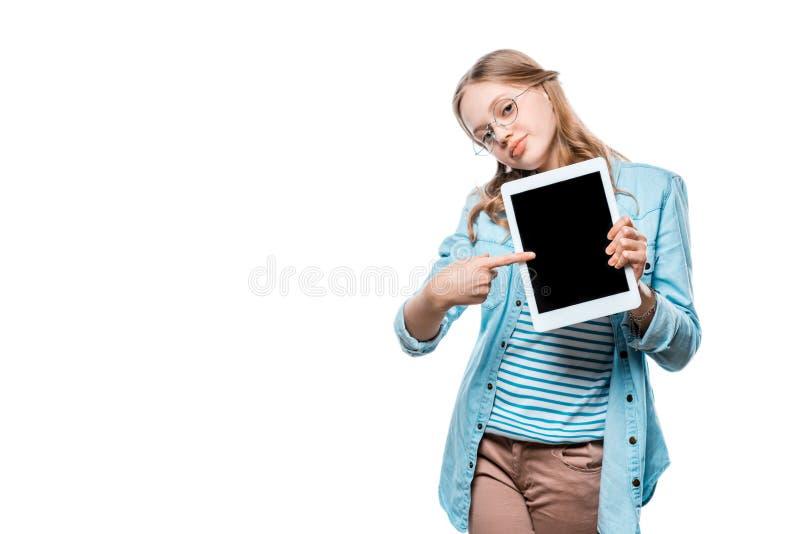 Uśmiechnięta nastoletnia dziewczyna trzyma cyfrową pastylkę i wskazuje z palcem przy pustym ekranem zdjęcie stock