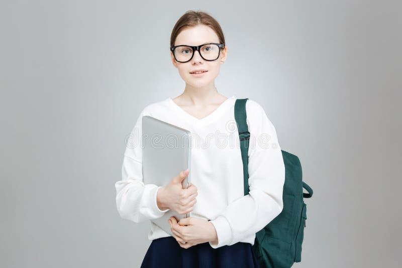 Uśmiechnięta nastoletnia dziewczyna trzyma zielonego plecaka i laptop w szkłach zdjęcie royalty free