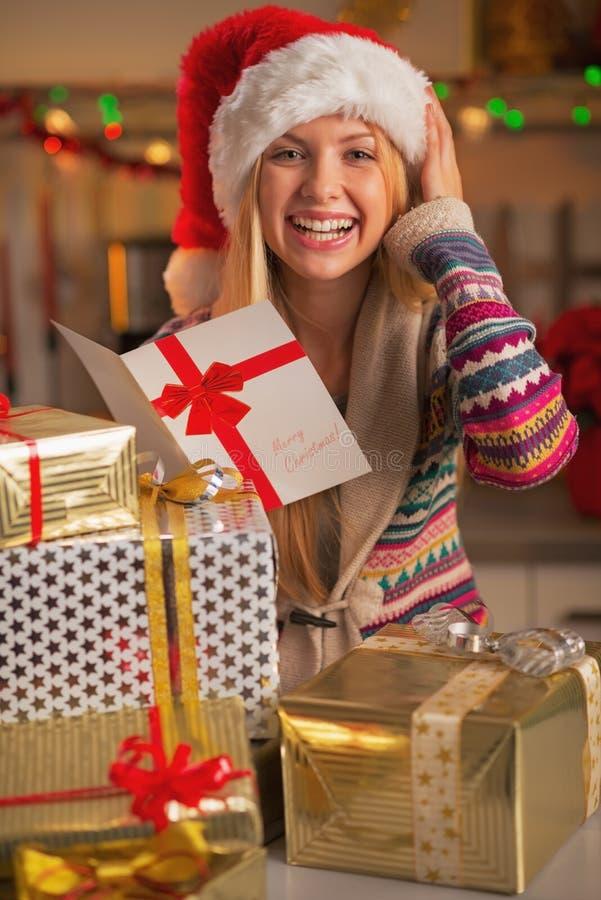 Uśmiechnięta nastoletnia dziewczyna w Santa kapeluszowych czytelniczych bożych narodzeniach pocztówkowych fotografia royalty free