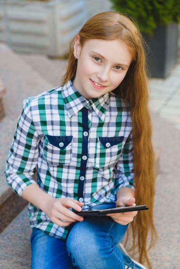 Uśmiechnięta nastoletnia dziewczyna z pastylka komputeru osobistego komputerem outdoors zdjęcia stock