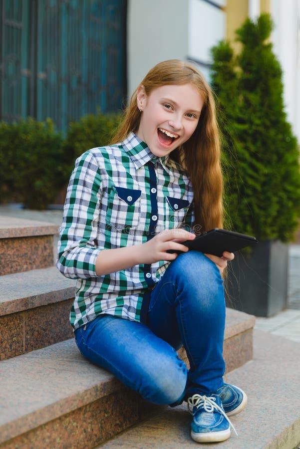 Uśmiechnięta nastoletnia dziewczyna z pastylka komputeru osobistego komputerem outdoors zdjęcie stock