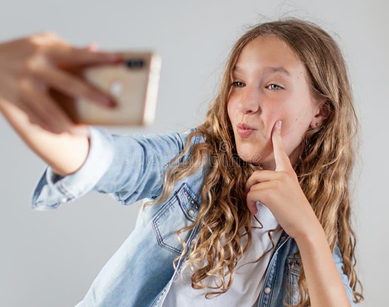 Uśmiechnięta nastoletnia robi selfie fotografia na smartphone nad białego tła śliczną dziewczyną obrazy royalty free