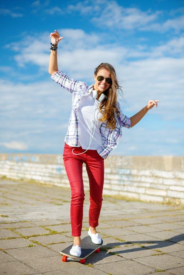 Uśmiechnięta nastoletniej dziewczyny jazdy łyżwa outside obraz royalty free
