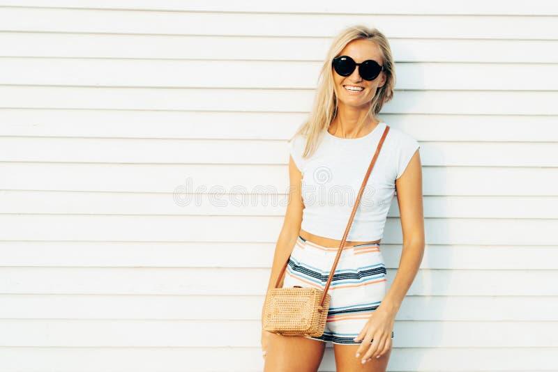 Uśmiechnięta nikła blondynka na letnim dniu w skrótach i okularach przeciwsłonecznych z modną słomianą torbą obraz stock