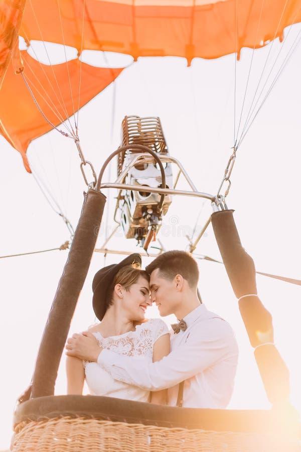 Uśmiechnięta nowożeńcy para ściska i stoi konfrontacyjna w airballoon koszu Góry zakończenia portret obrazy stock