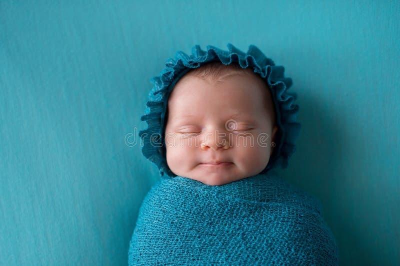 Uśmiechnięta Nowonarodzona dziewczynka Jest ubranym Turkusowego błękita czapeczkę obraz royalty free