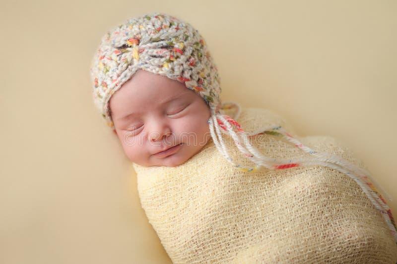 Uśmiechnięta Nowonarodzona dziewczynka Swaddled w kolorze żółtym fotografia royalty free