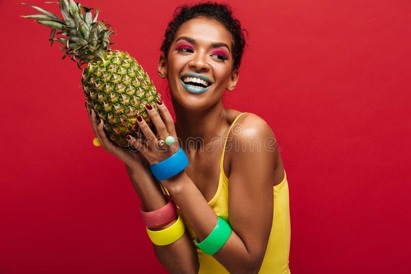 Uśmiechnięta oliwkowa kobieta z mody makeup w żółtym koszulowym enjoyi fotografia royalty free