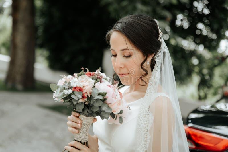 Uśmiechnięta panna młoda w ślubnej sukni i przesłona, spojrzenia przy ślubnym bukietem zdjęcia stock