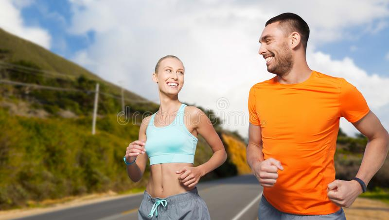 Uśmiechnięta para biega nad dużymi sur wzgórzami fotografia stock